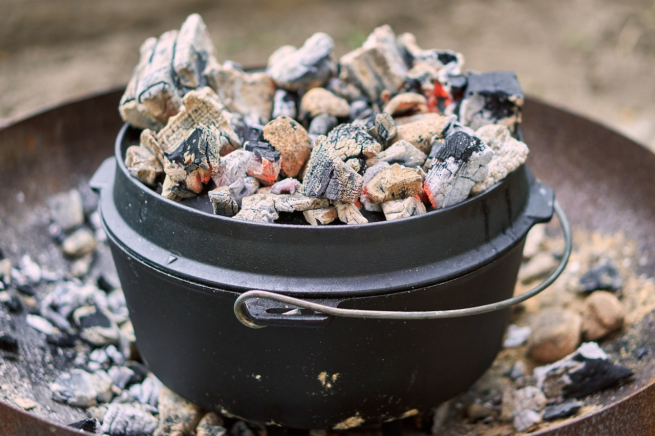 Front view of a black cast iron dutch oven filled with warm coals on top and resting over a mini barbecue grill - 5 Hearty Vegan Recipes