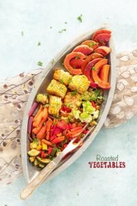 Top view of roasted veggies in silver eye-shaped bowl with a grill fork on the side