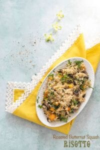 Top view of a risotto filled white oval plate over a yellow lace napkin