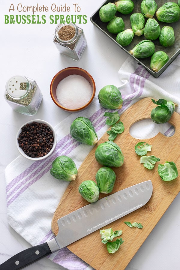 Top view of Brussels sprouts on a cutting board on cloth with a large cutting knife and seasonings around it.