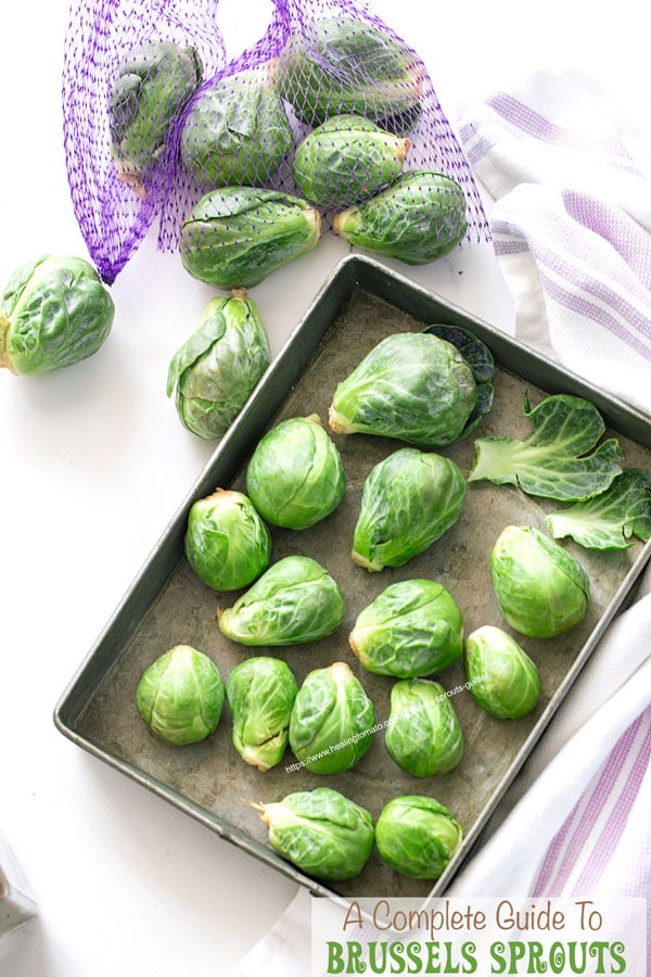 A grey tray filled with brussels sprouts and a purple mesh bag filled with Brussels sprouts next to it