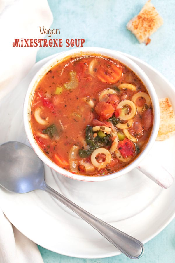 A closeup view of a cup filled with minestrone soup is on a plate and croutons strewn about