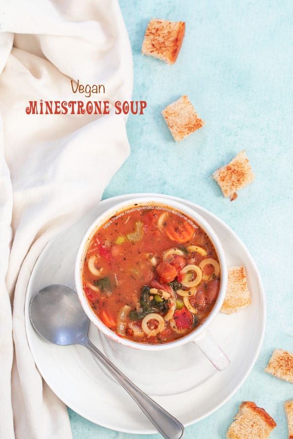 A top view of a cup filled with minestrone soup is on a plate and croutons strewn about