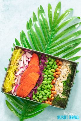 Top view of a rectangle metal tray on a long palm leaf. Metal tray has the following ingredients arranged in a row: shredded mango, radishes, potatoasts, red cabbage kraut, edamame, chickpea snack, riced cauliflower and seaweed squares