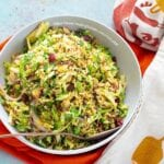 Top view of a grey bowl with Brussels sprouts pilaf over orange and white cloths