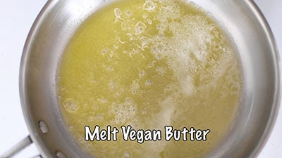 Vegan butter melted in a stainless steel pan