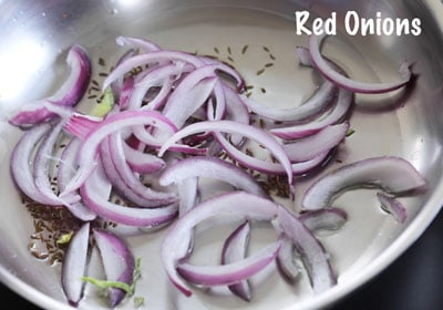 red onion strips added to the pan