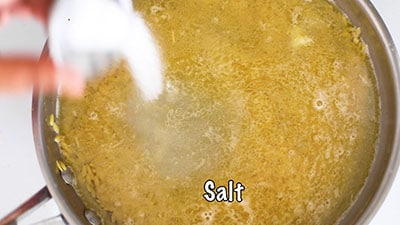 The author's hand pouring salt from a tiny bowl