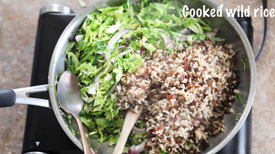Cooked wild rice added to the pan with the sprouts