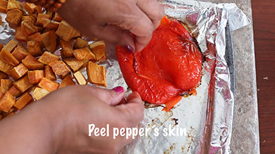 The author's hand peeling the red bell pepper