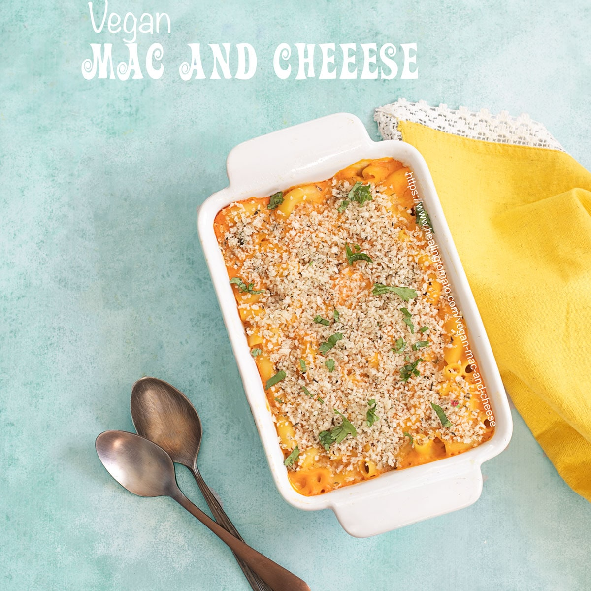 Top view of a white casserole dish on blue background and a yellow cloth on the side. Casserole dish is filled with vegan Mac and cheese