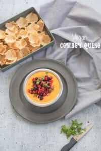 Top view of a stainless steel bowl filled with cowboy queso placed on a gray dish. There is a gray tray next to it filled with tostios scoop chips