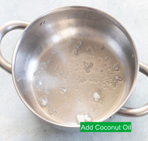 Top view of coconut oil added to a stainless steel sauce pan