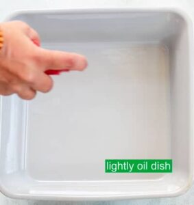 The author's hand visible holding an oil spray bottle, spraying a grey square baking dish