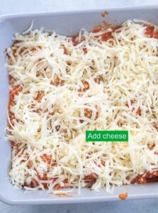 Top view of shredded pepper jack cheese added to the grey baking dish