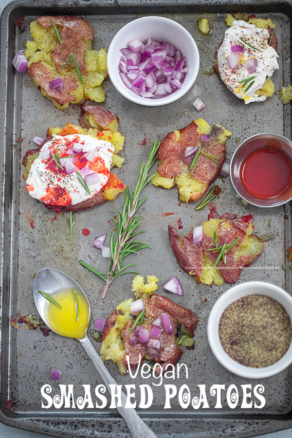 Top view of 6 baby smashed potatoes on a grey baking tray garnished with red onions, rosemary leaves and sour cream.