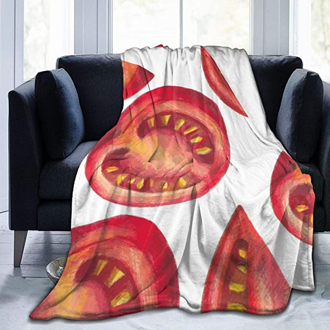 a white blanket designed with cut tomatoes thrown on a couch