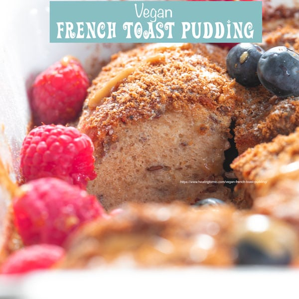 Front view of a crossection of the bread pudding in a baking with raspberries and blueberries on the side