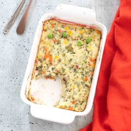 Top view of a white baking dish filled with mashed potato and vegetables souffle and a section cut out
