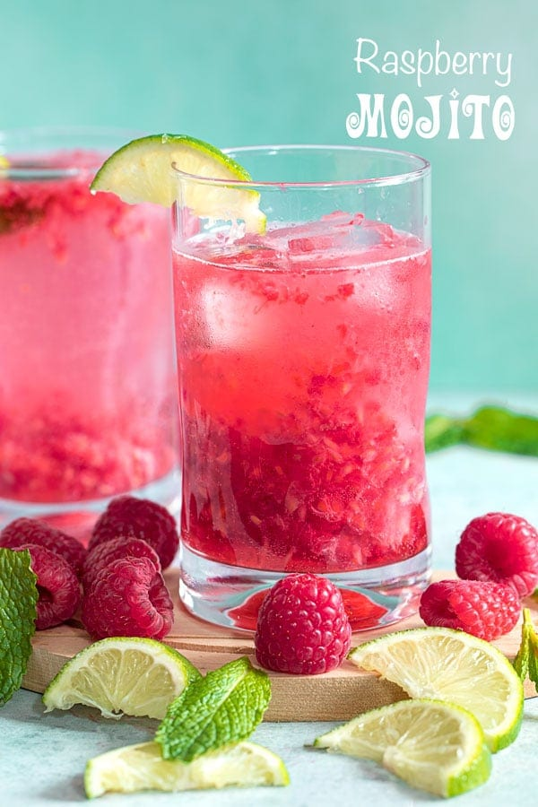 Front and closeup view of a small glass with raspberry mojito surrounded with lime slices, mint and raspberries