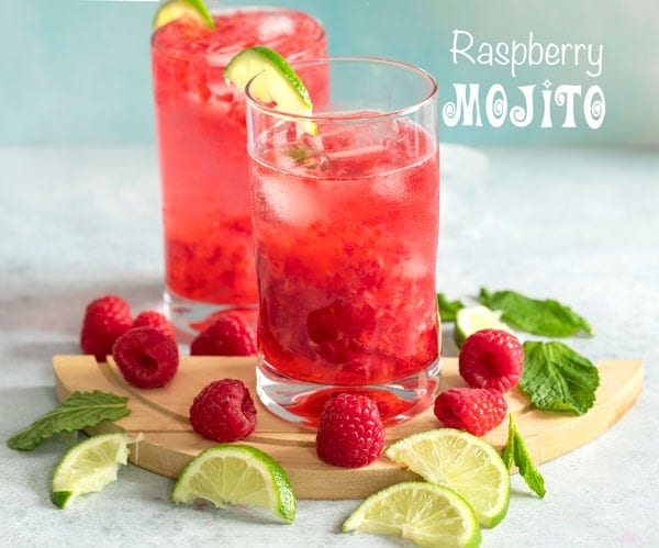 Front view of two small glasses with raspberry mojito surrounded with lime slices, mint and raspberries