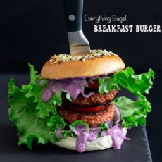 Front view of the double decker everything bagel brekafast burger on a light black stone tray with a knife handle sticking out of the top of the bagel