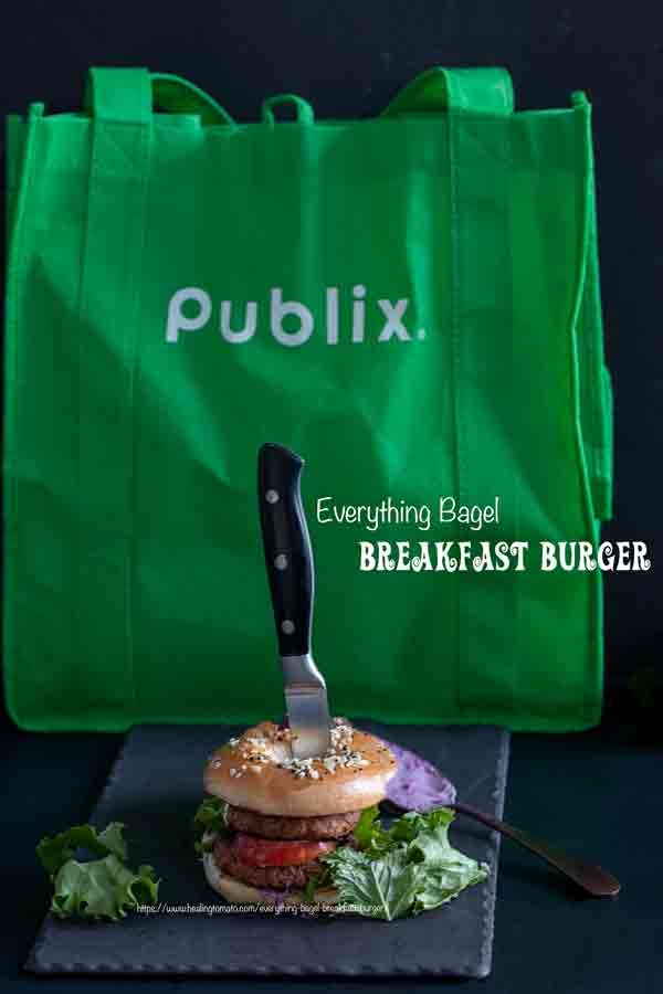 Front view of the breakfast bagel on a grey tray with the Publix shopping bag in the background