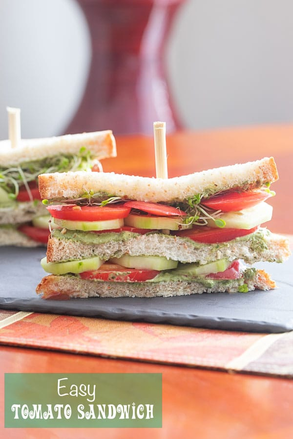 Front view of a double decker tomato sandwich with layers of tomato, cucumber, pesto spread and broccoli sprouts