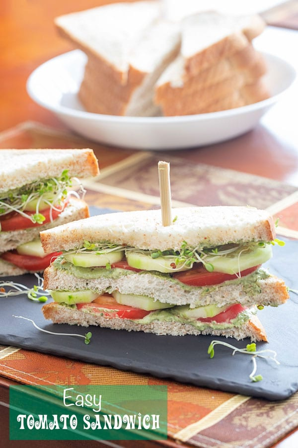 Front view of a double decker tomato sandwich with layers of tomato, cucumber, pesto spread and broccoli sprouts. A bowl of sliced bread is visible in the background