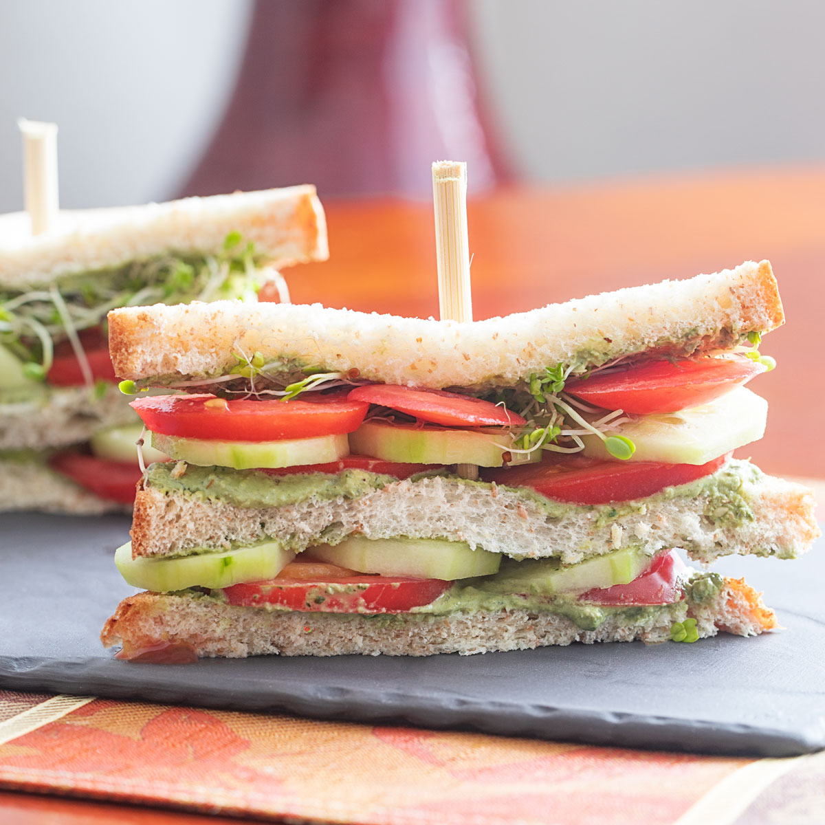 Closeup view of a double decker tomato sandwich with layers of tomato, cucumber, pesto spread and broccoli sprouts