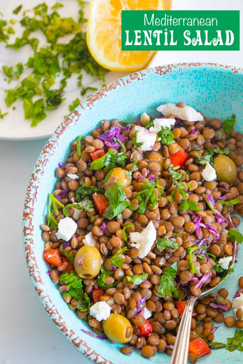Top view of lentil salad in a light blue bowl with a spoon next to it