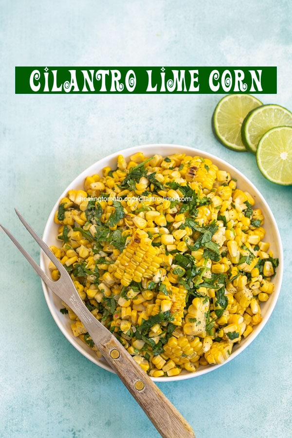 Top view of a bowl filled with grilled corn with a 2 pronged grilling fork on the side and 3 lime slices