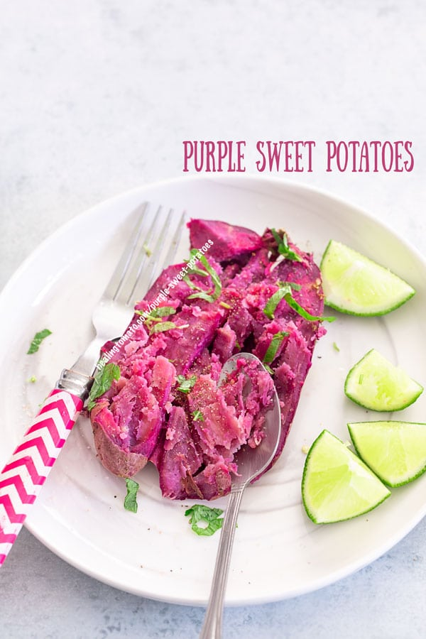 top view of a baked purple sweet potato on a white place with a spoon on the side and a fork on the left. Lemon pieces on the plate too.