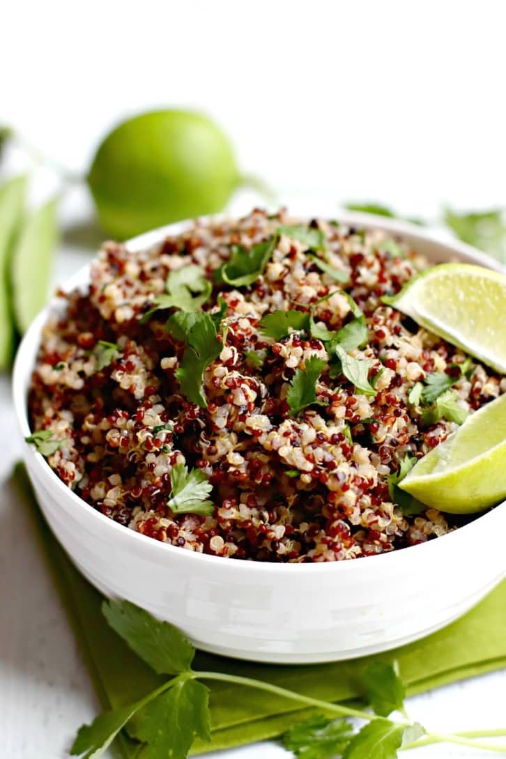 top view of a white bowl with quinoa and cilantro lime garnish