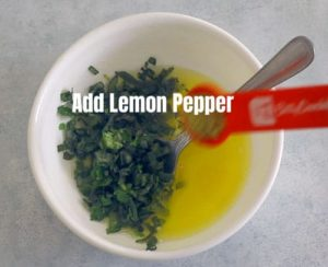 top view of a red measuring spoon adding lemon pepper to a white bowl with butter + herbs