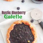Top view of a blueberry galette with puff pastry crust and a pizza cutter on the side with blueberries.
