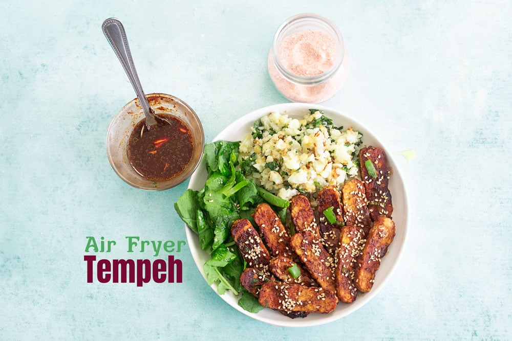 Top, landscape view of tempeh in a budda bowl with greens and rice