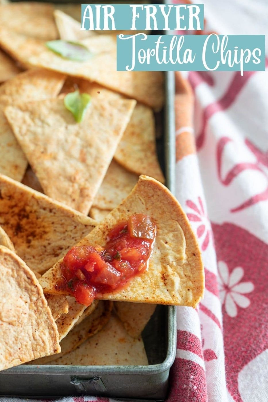 top, closeup view of a tortilla chip with salsa on it on top other tortilla chips in a grey pan