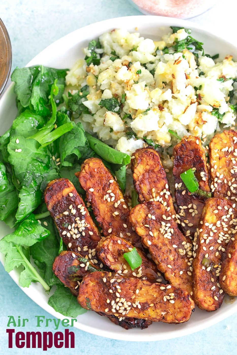 Top closeup view of tempeh in a bowl with sesame seeds for garnish