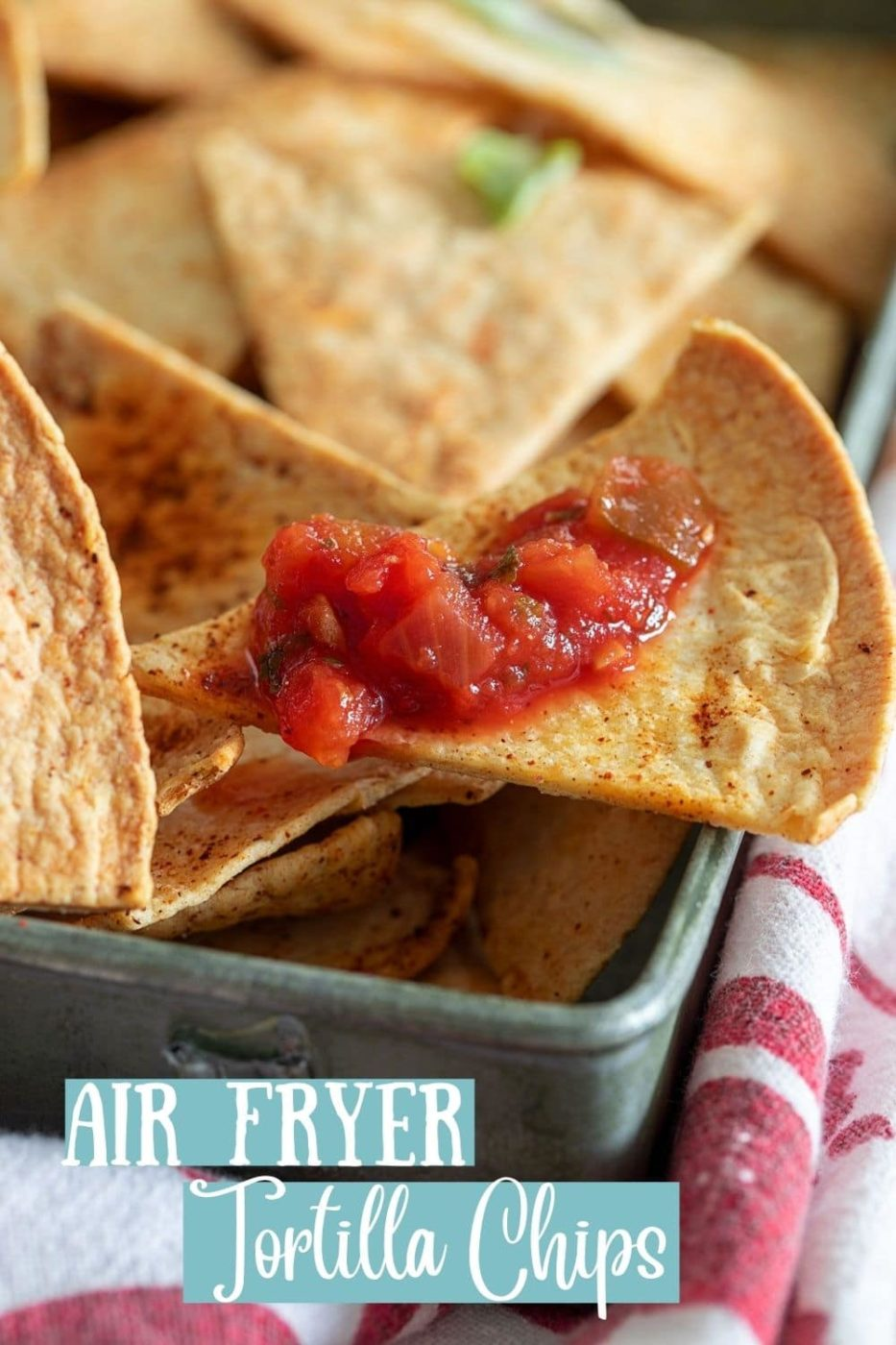 side view of a tortilla chip with salsa sitting on the edge of a grey pan. Grey pan is filled with tortilla chips