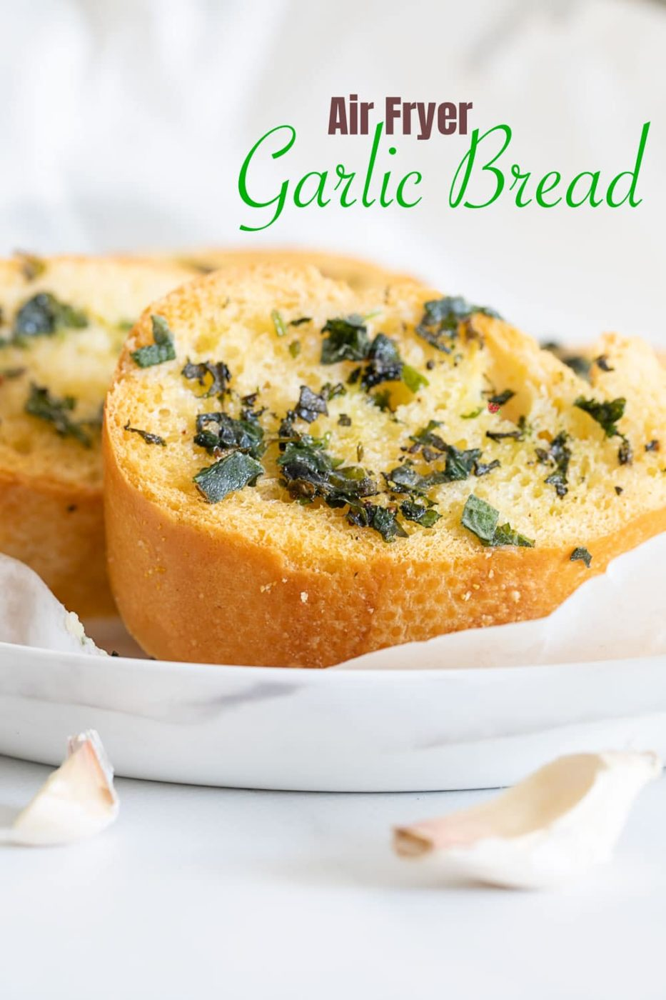 Side view of a slice of garlic bread on white plate
