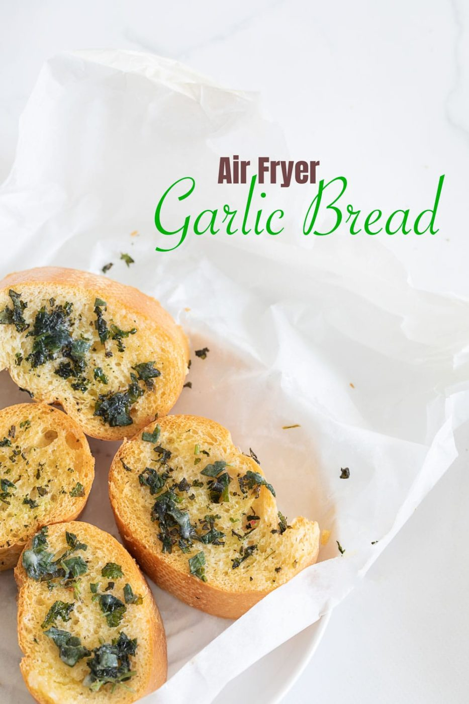 Top view of garlic bread on wax paper and white plate placed on the left corner of the image.
