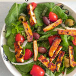 A bowl of tofu salad where the roasted tofu is cut into small, rectangle slices