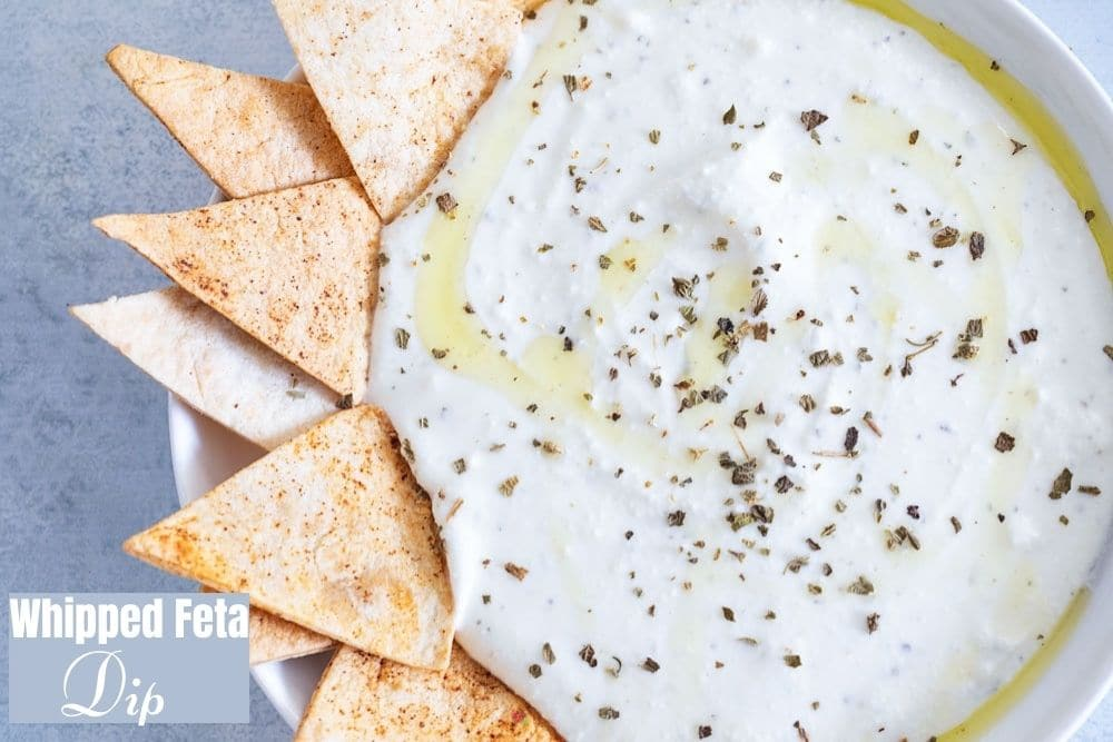 Closeup view of a white bowl filled with the whipped feta bowl with oil and seasoning as garnish. The left side of the plate is decorated with tortilla chips