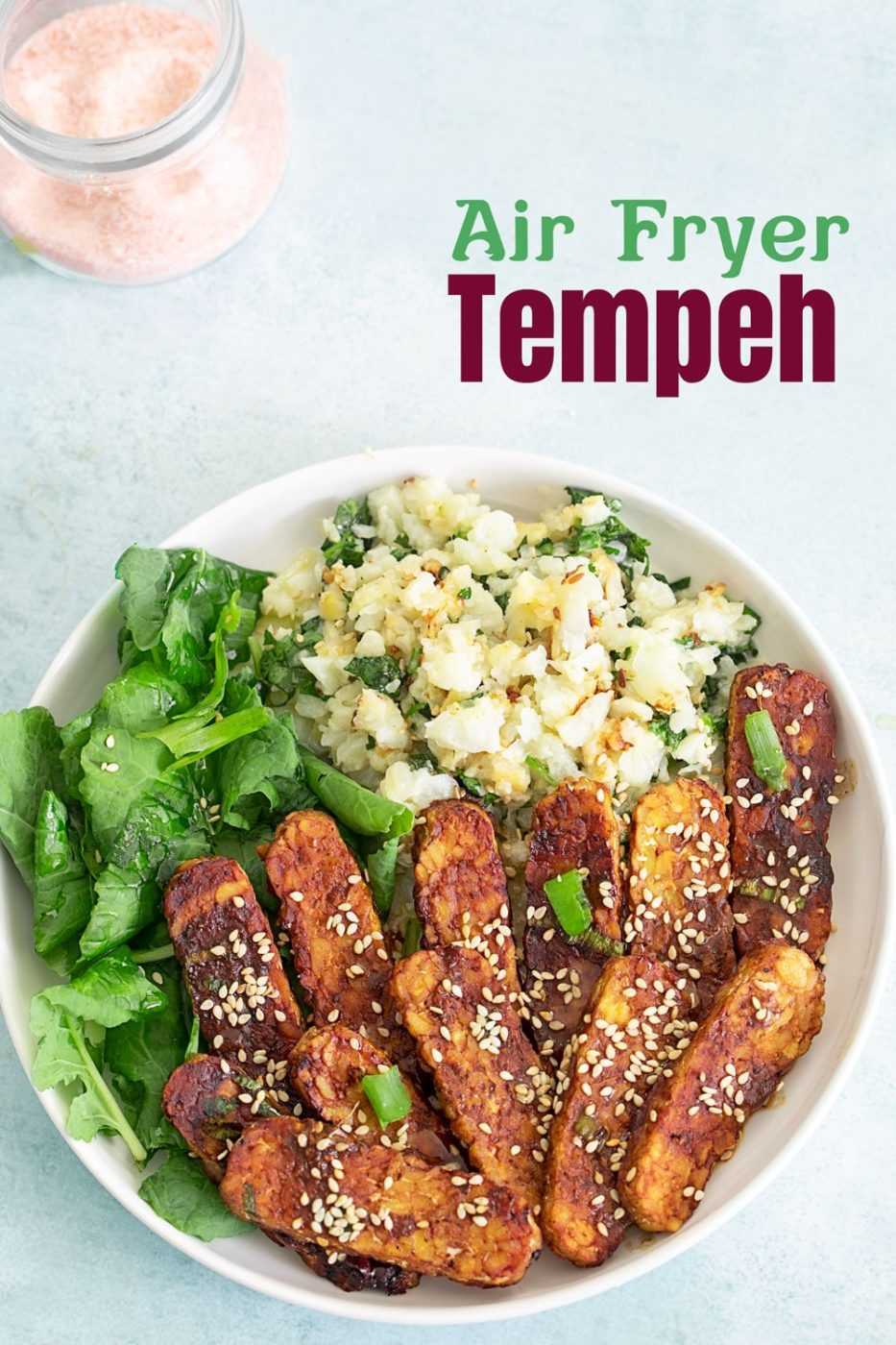 Top view of a vegan buddha bowl with air fryer tempeh, greens and rice
