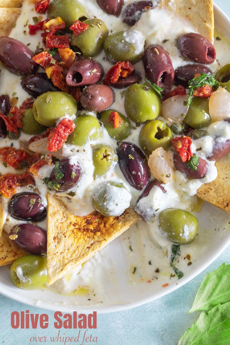 Top view of olive salad on a whipped feta dip. A chip is in the process of scooping up the dip
