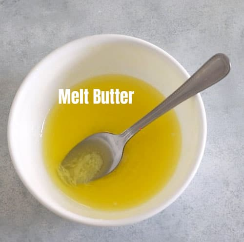 melted butter in a white bowl with a spoon in it.