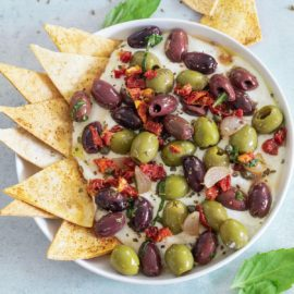 Top, closeup view of olive salad on a whipped feta dip with a tortilla chips on inserted on the left side of the dip