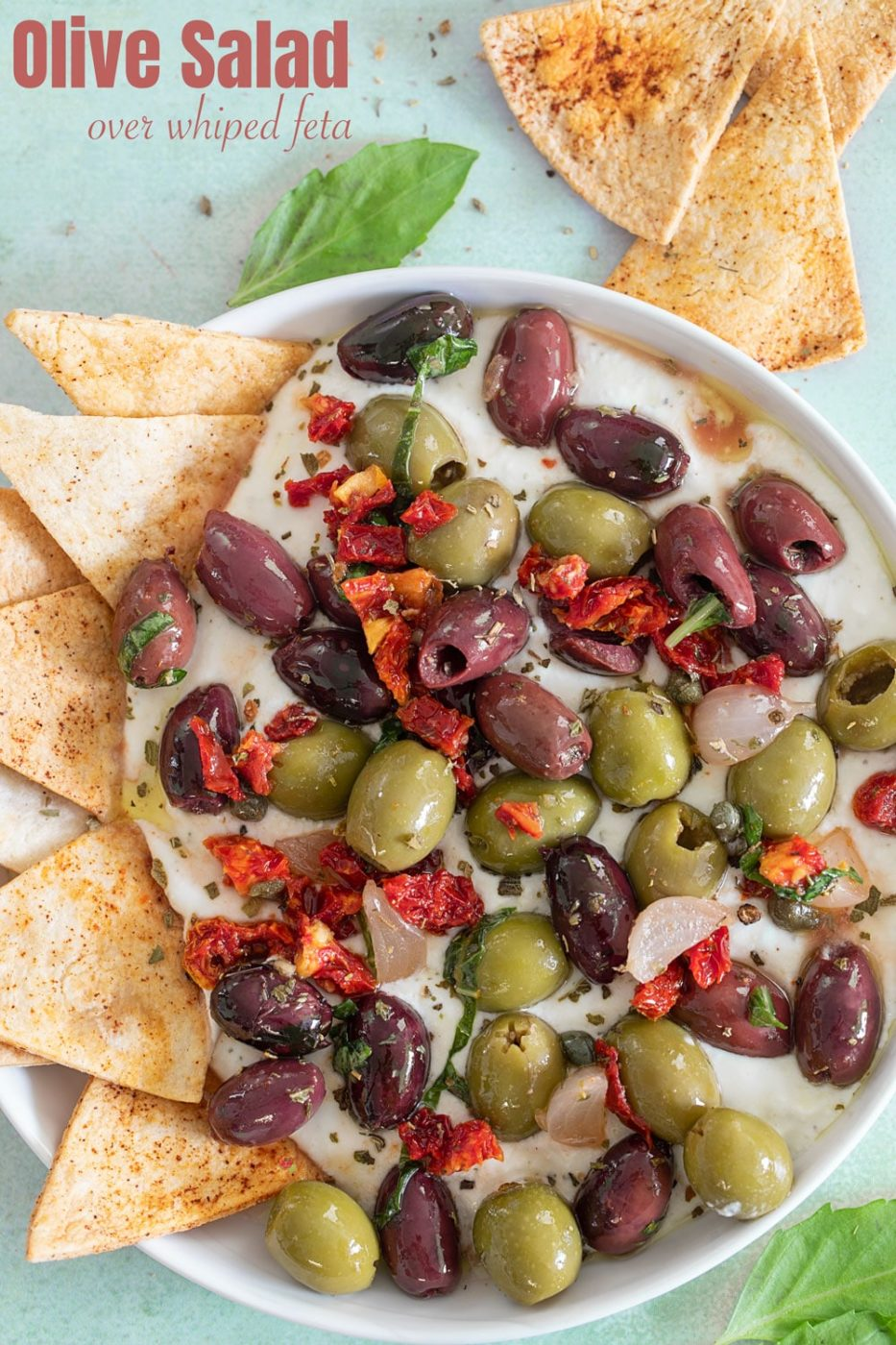 Top view of olive salad on a whipped feta dip with a tortilla chips on inserted on the left side of the dip