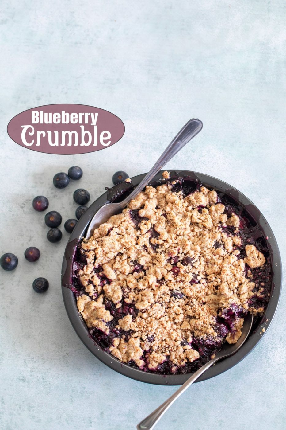 overhead view of the pie crumble in a pan with a spoon in it. On the side, there are fresh berries.